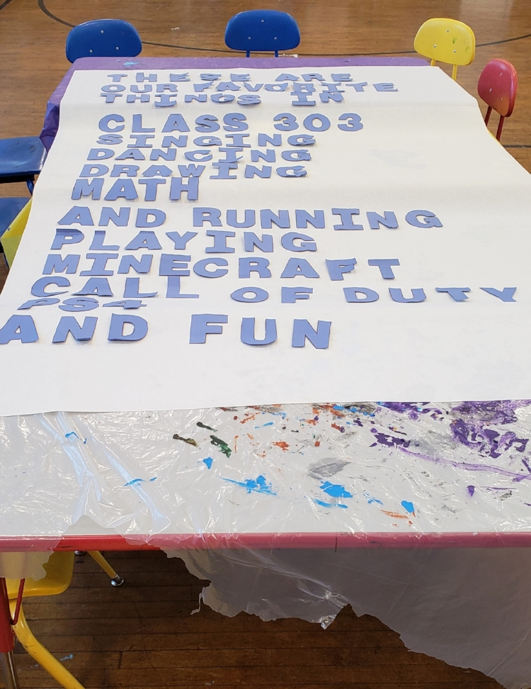 "White mural paper with the poem in blue construction paper letters laid out on tables covered in plastic. The poem reads ""These are / our favorite / things in / class 303 / Singing / Dancing / Drawing / Math / And running / playing Minecraft / call of duty / PS4 / and Fun"""