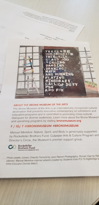 Small paper flyer on a white table. The flyer has a photograph of the large, mural, praise poem in situ at the school against a brick wall with other art projects surrounding it. Below the photo is a description of the Bronx Museum, it's social media content, and the funders/donors.