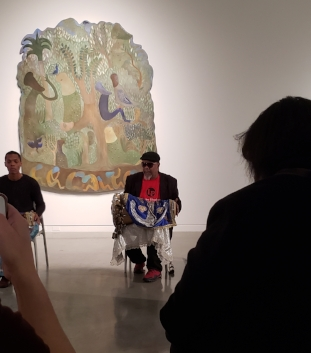 Two afro-cuban men play drums. The one on the left is younger and bit cut off by the frame. On the right is Roman Diaz, he is an older man, wearing a black berret, sunglasses, a red shirt and a black blazer. His large drum is horizontal across his lap and covered in a decorative blue, white and gold cloth. In the foreground are audience members, one holding up a phone to film. In the background is artwork by Manuel Mendive on a white museum wall. The art has a jungle like scene where humanoid figures are sitting on, around, and underneath a tree.