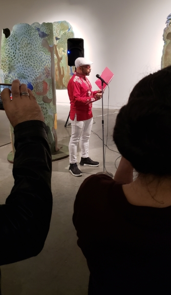 Afro-Cuban Poet Orlando Ferrand reads into a microphone from a red folder. He is wearing all white beret, glasses, a red shirt, white pants and black sneakers. In the foreground are audience members holding phones up to film and take pictures. The background is the Mendvie exhibit. No single piece of art is all in frame, but the nature elements of Mendive are clear with trees, leaves, roots, birds, jungle like plants, and human figures all visible in blues, greens, red, yellows, and browns.