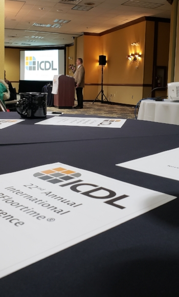 Jeff Guenzel a middle aged white male with professionally dressed addresses an audience from behind a podium. In the foreground is a table with a conference flyer and in the background, behind Guenzel, is the ICDL logo on a power point screen. Around Guenzel can be seen equipment such as projector, speakers, lights. The walls of the hotel lobby are yellow and the floor has a navy and yellow rug to match.
