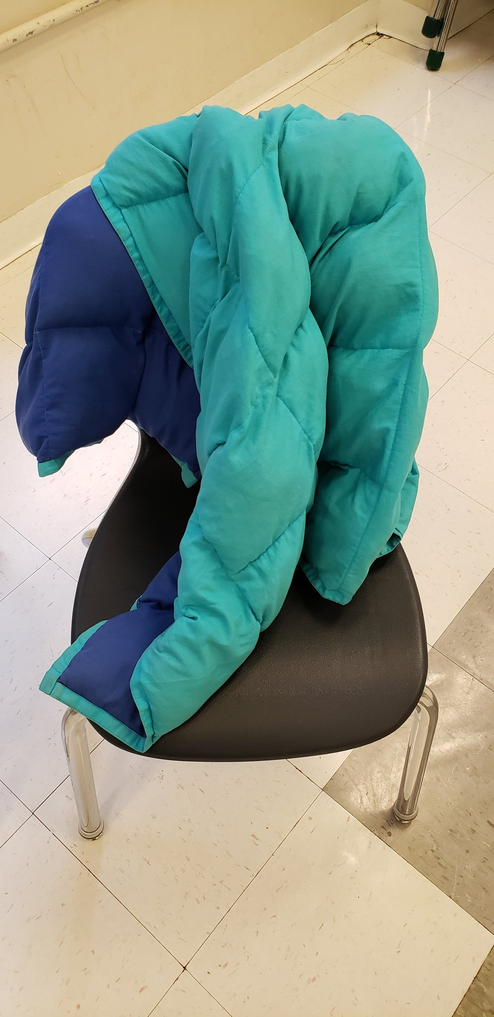 Teal and dark blue weighted blanket sitting on top of a black chair in a tiled classroom.