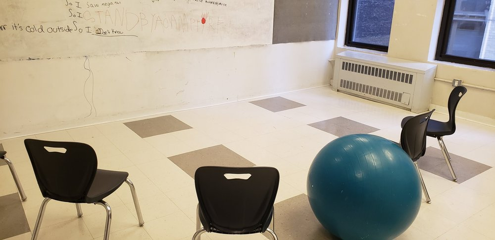 Tiled classroom with a white board. Black chairs arranged in a half-circle around the white board. In the middle of the chairs is a teal yoga ball intended to be a seat. On the board can be seen some writing.