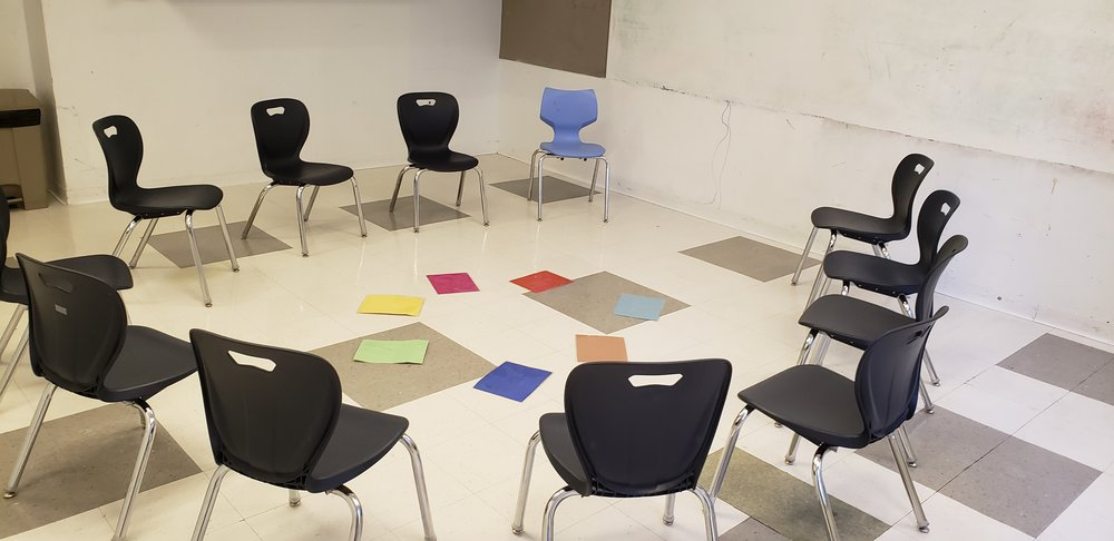 A circle of classrrom chairs, black and one blue, on a tiled floor. In the middle of the circle of chairs is a smaller circle of colored cards. In the foreground is a classroom dry-erase whiteboard.