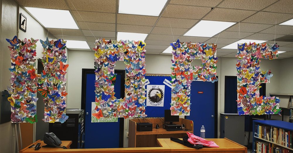 "The word ""hope"" spelled out in large, capital letters cut from poster paper and suspended in a school library. Inside the letters are butterflies of various colors crafted out of paper."