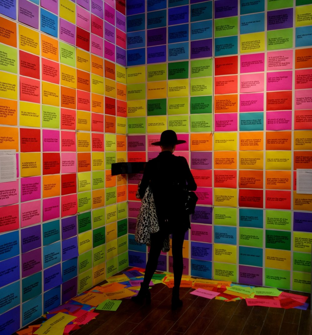 """Additional installation view. Along with the 256 text elements themselves, the 25 colors represent both the breadth and varying intensity of the artist's bipolar 1 thoughts and feelings on a particular subject when in a hypomanic (mild mania) state, thus providing the viewer with a proximate experience of having an """"abnormal"""" mind. The artist recorded the amount of time his mind took to generate the 256 text statements and questions. All 256 elements came into his mind in less than 30 seconds of real time during a particularly productive hypomania."""