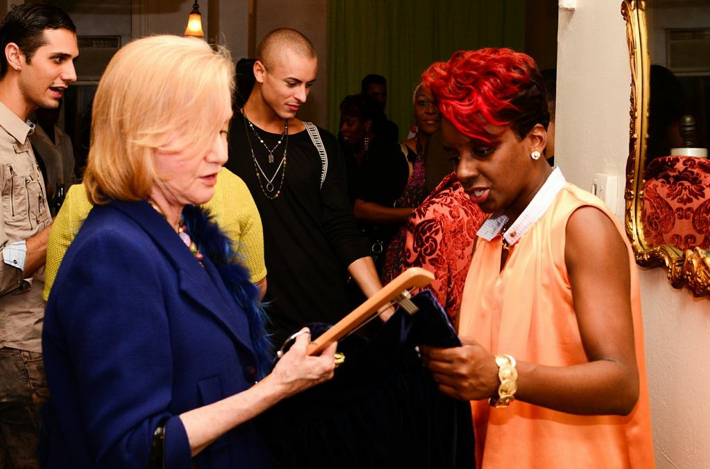 Designer Kera Anderson showing a guest a piece from her latest collection