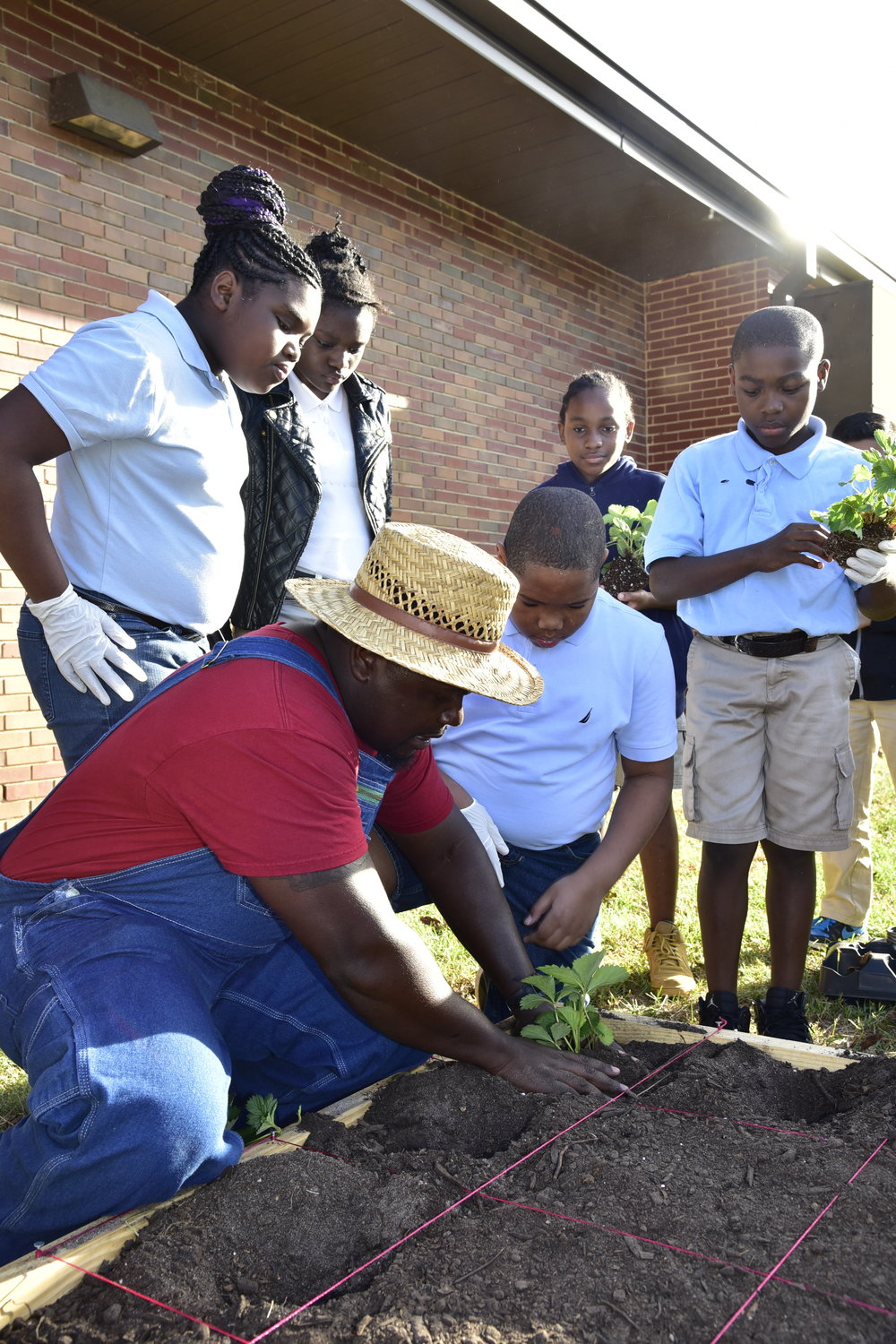 "Photo:  Flint River Fresh Executive Director, Fredando ""Farmer Fredo"" Jackson, planting strawberries with students from Radium Springs Elementary in their teaching garden. (Todd Stone Photography)"
