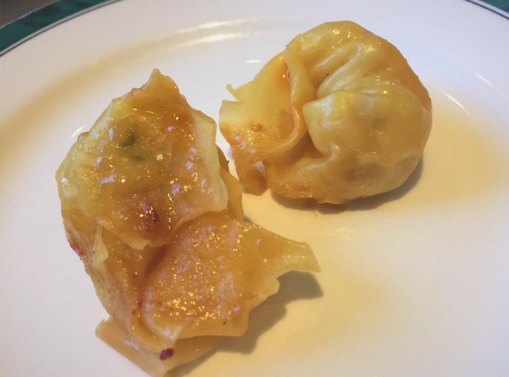 A zoomed-in shot of the golden dumplings, without a ton of sauce on them. The inconsistent noodle shape also suggests that these are homemade.