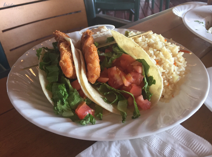 Two soft shell tacos filled with white fish breaded in panko crumbs, topped with lettuce, tomato, and tartar sauce, served with wild rice.