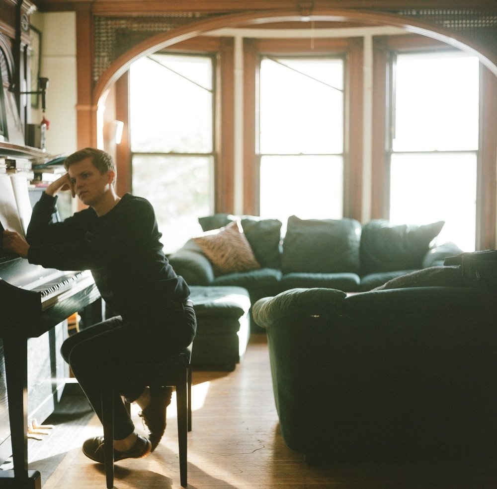 Daniel looks deep in thought at the piano in the living room, shot on a Mamiya C330 with Kodak Portra 120, 2017