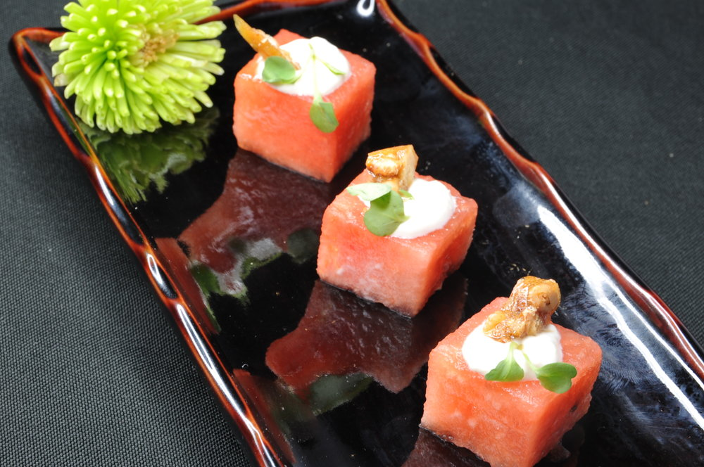 "Watermelon cube with cashew ""goat"" cheese, pine nut brittle, and micro basil"