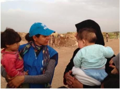 Tala at the Jordanian-Syrian border with a Syrian family.     Photo Credit: Sebastian Rich/UNHCR