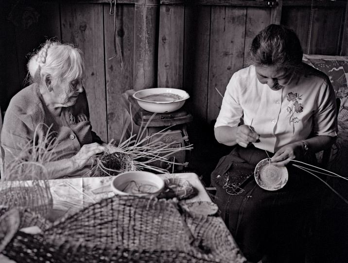 "Maidu Basket Weavers by Philip Hyde Photograph Description  By David Leland Hyde, Dec 30, 2018  In 1963, while Maidu Basket Weavers Daisy Baker and her daughter Lilly Baker made baskets at Daisy's home in Indian Valley near Greenville, California, American conservation photographer Philip Hyde documented the ladies work with a series of medium format 2 1/4 film photographs. Daisy Baker died just a few months after the photo session, though Lilly Baker lived until age 95 in 2006. Both Daisy and Lilly made Maidu baskets for many years and taught others the skill, but none have produced the number or variety of shapes and sizes that the Bakers did. Some historians have called them, ""the last of the Maidu Basket Weavers."" Besides her childhood home in Big Meadows, now mainly submerged by Lake Almanor, two of Lilly's favorite places to cut and gather willows for baskets were along Indian Creek in Mormon Canyon between Taylorsville and Genesee and at the Mouth of Genesee Valley. Sets of the Maidu Basket Weavers 10 photograph series of original sliver gelatin prints can be found in permanent collections at the Oakland Museum, The Maidu Museum Interpretive Center and Historic Site, The Redding Museum, Plumas County Museum, Greenville Cy Hall Memorial Museum and Indian Valley Museum."