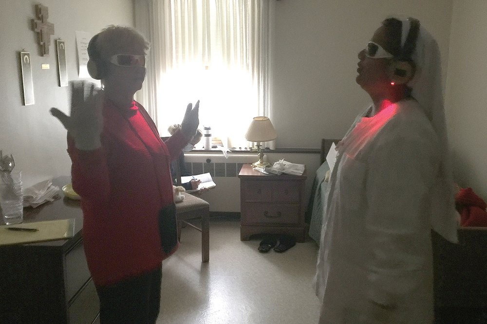 Kate Guay, assistant administrator, and Sister Beena Jose, a nurse in Antonia Hall, take part in the Virtual Dimentia Tour.