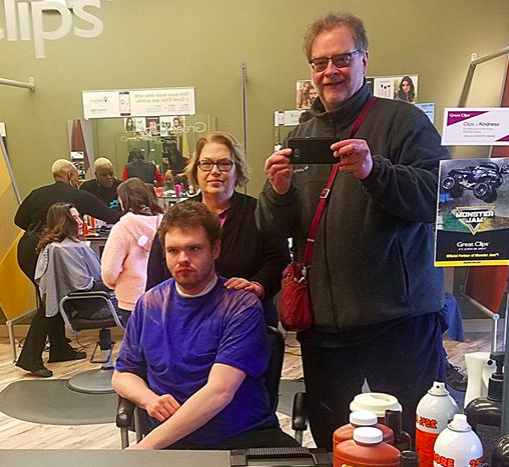 In a recent photo, Ben, seated, gets ready for a haircut while dad David snaps the pic.