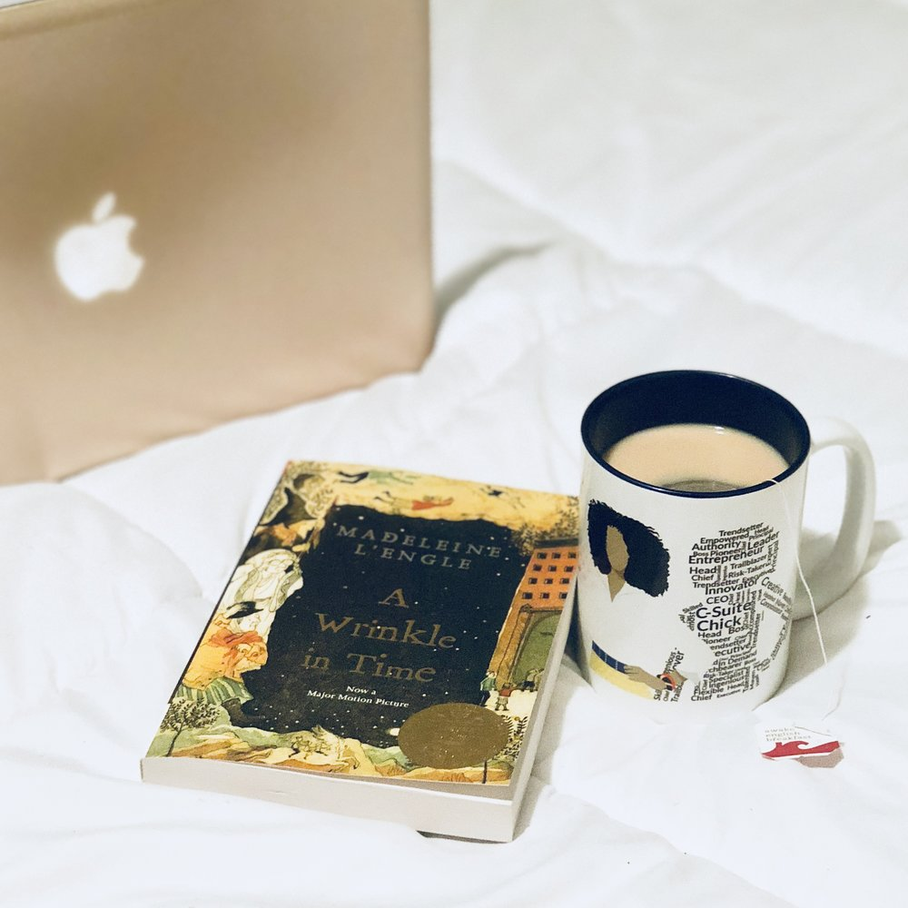 finding my moment of hygge in bed with the book A Wrinkle in Time and hot tea
