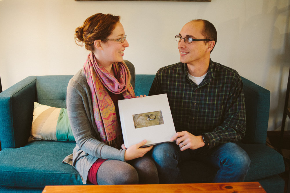 Melissa Andrew hold their wedding album by Alyssa Lund Photography.jpg