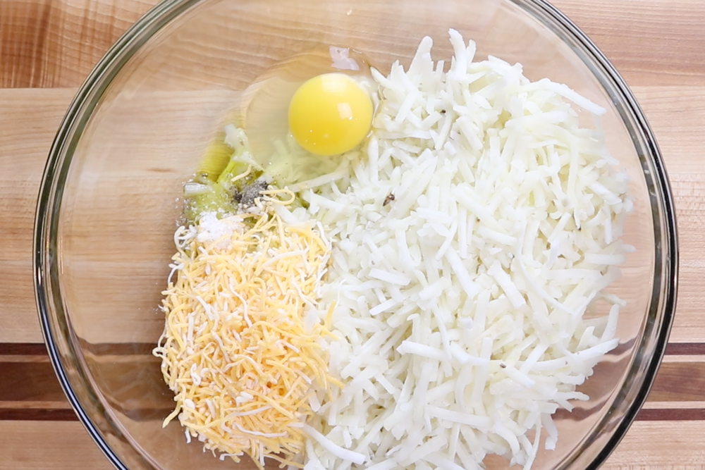 1. Combine one egg with hash browns, olive oil, 1/2 cup shredded cheese and salt and pepper. -