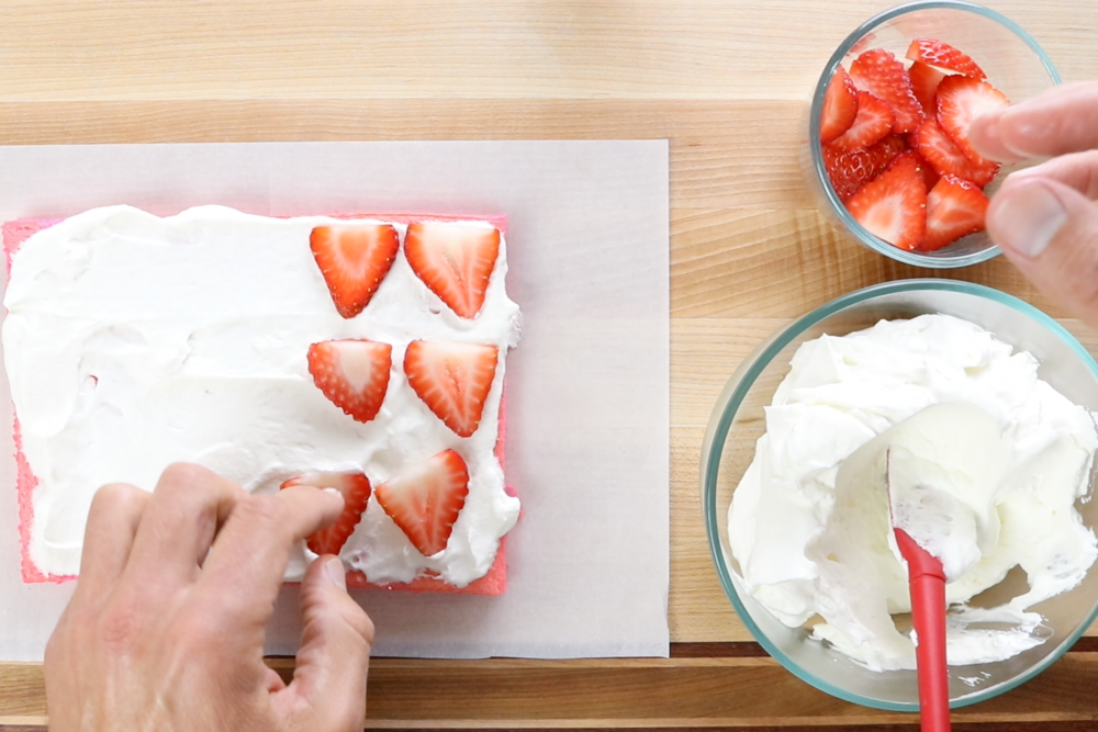 1.  Frost the top of the cake with about ¼ of the whipped cream. Lay strawberry slices on top of the cream.  -