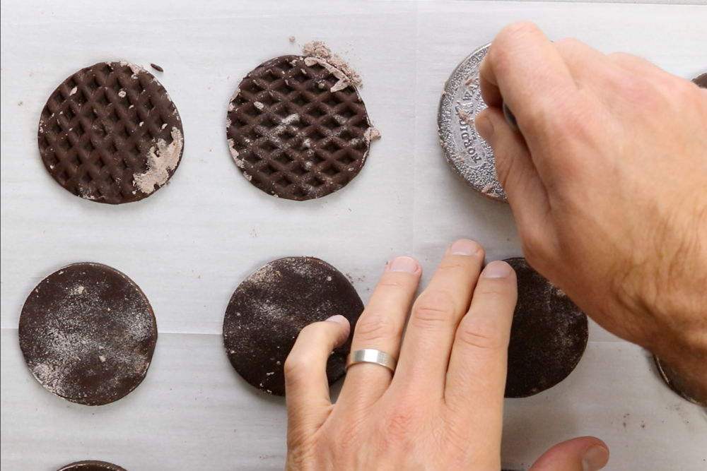 9. If you have a cookie stamp, press it firmly into the top of each cookie to make an impression. If it is sticking, dust it lightly with cocoa/flour powder in between cookies. -