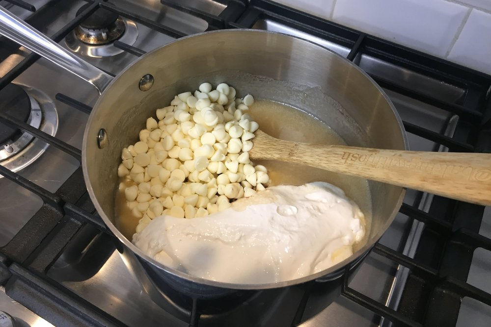 4. Remove from heat and add the marshmallow crème, white chocolate chips and vanilla. Stir until smooth. -