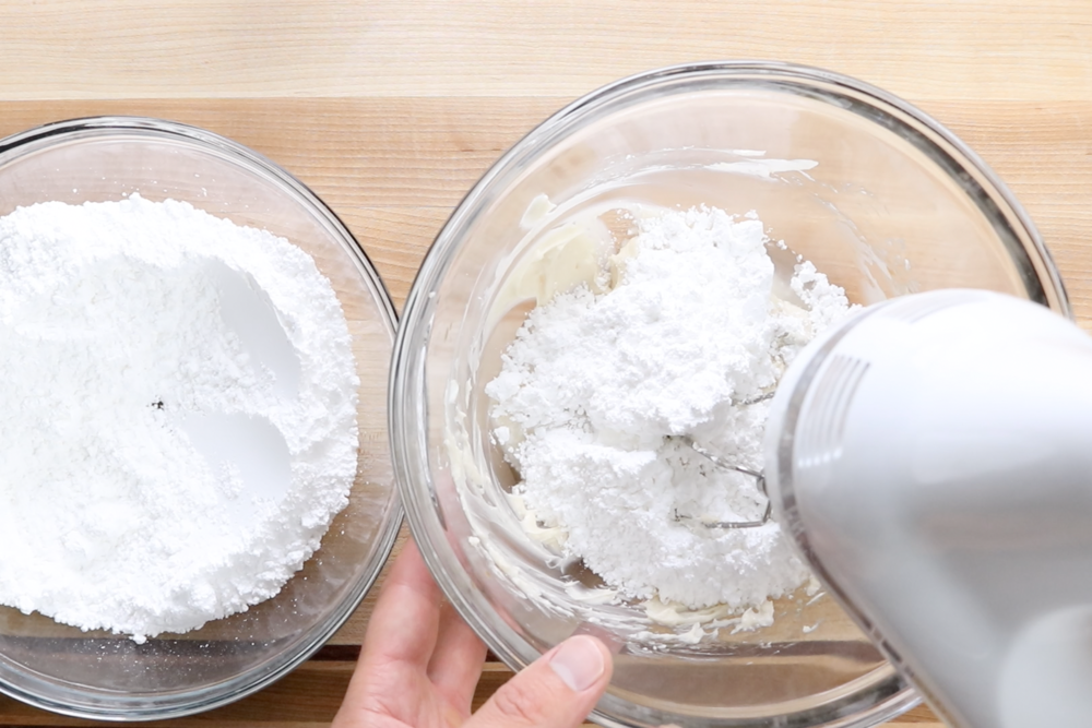 2.  Add half the powdered sugar and half of the water.  Mix on low speed until incorporated scraping down the edges when necessary.   Put mixer on medium speed and blend well.  -