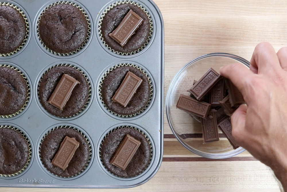 10. Bake for 12 minutes. Remove from oven and place 1 chocolate square in the middle of each cupcake. -