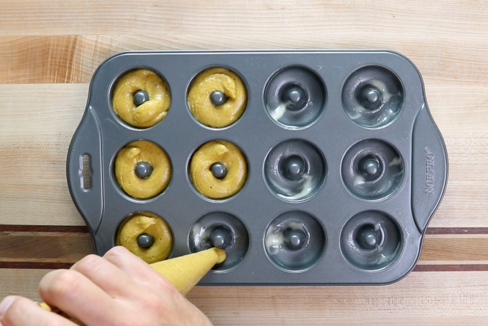 6. Pour batter into a piping bag and squeeze the batter into the mini-donut forms filling about ¾ of the way to the top. -