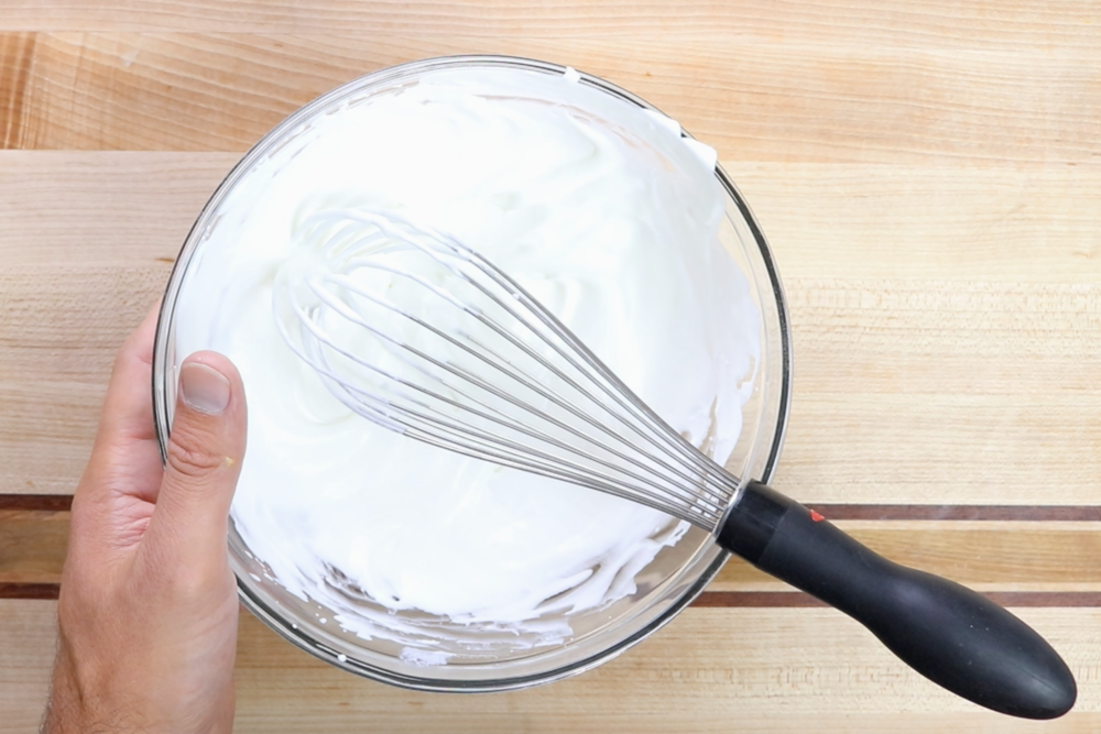 6. In a separate bowl, whisk the heavy whipping cream until stiff peaks form. -