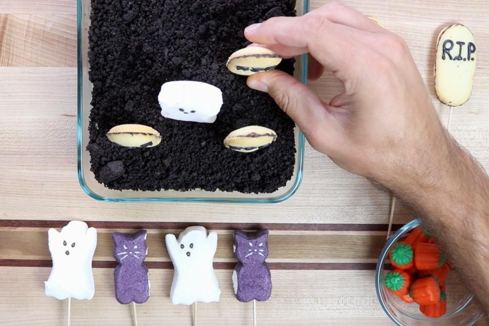 11. Use toothpicks to stick Milano cookies and marshmallow ghosts into the Oreo and pumpkin mixture. -