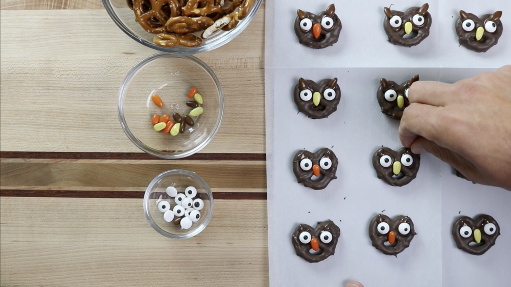 9. Squeeze two small amounts of chocolate on the top right and left sides of the pretzels and add the brown candy as ears. -