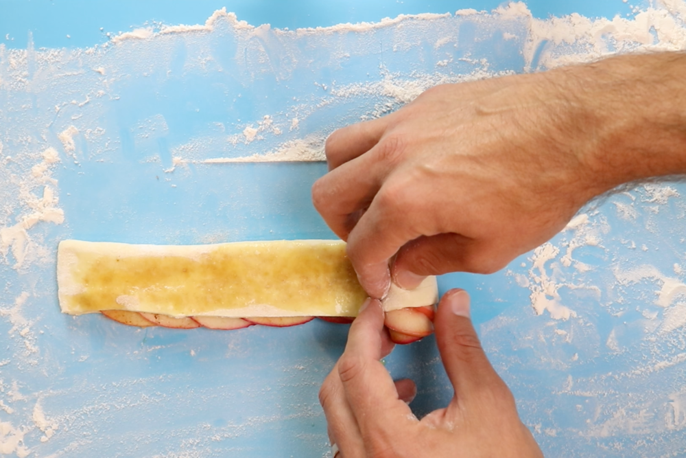 12. Starting at the end carefully roll the dough into a loose roll keeping the apple slices in place. Seal the edge at the end. -
