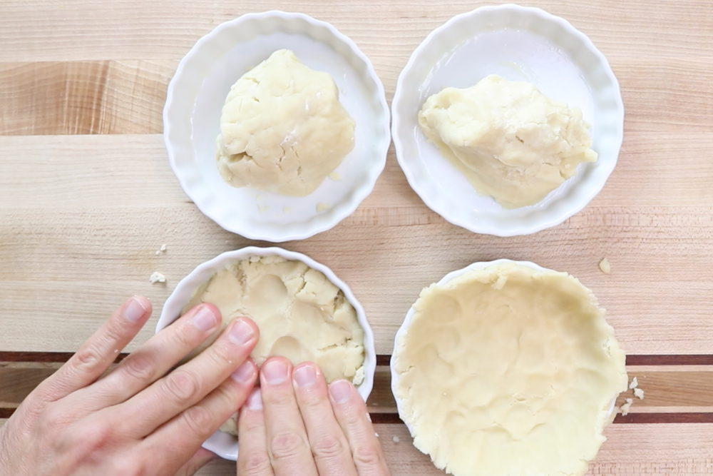 5. Divide dough into 4 pieces and press dough onto bottom & up the sides of your 6 oz quiche ramekins. -