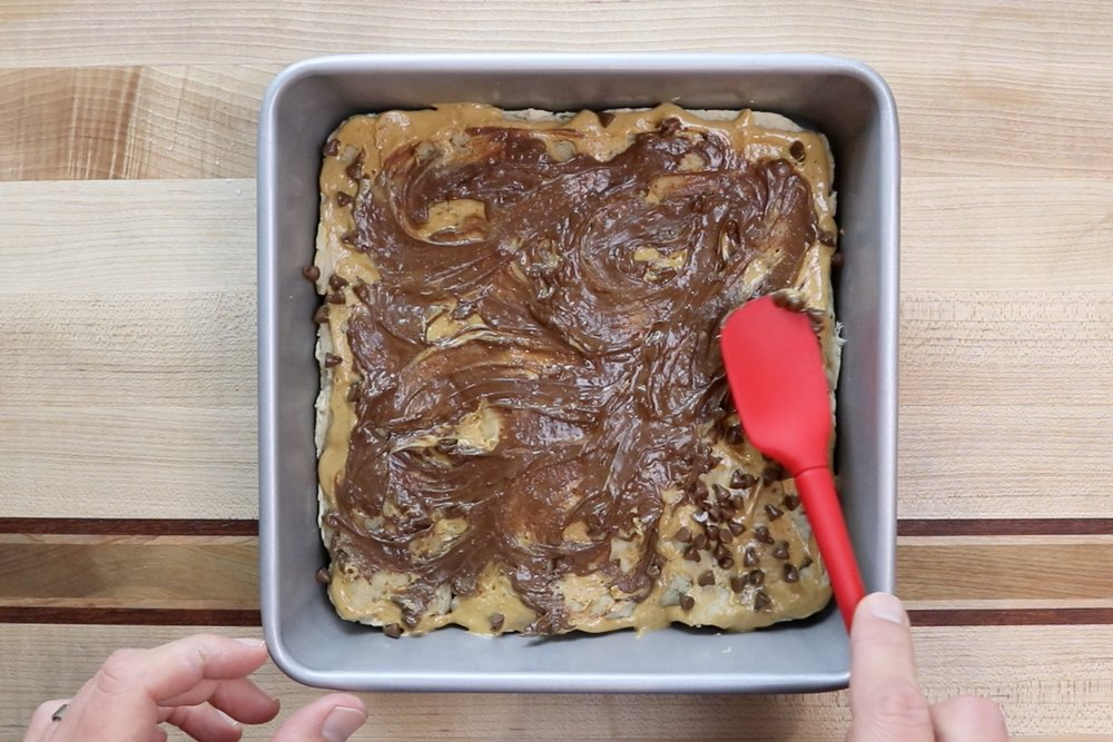 9. Take out of the oven and gently spread melted chocolate over the top of the brownies. -