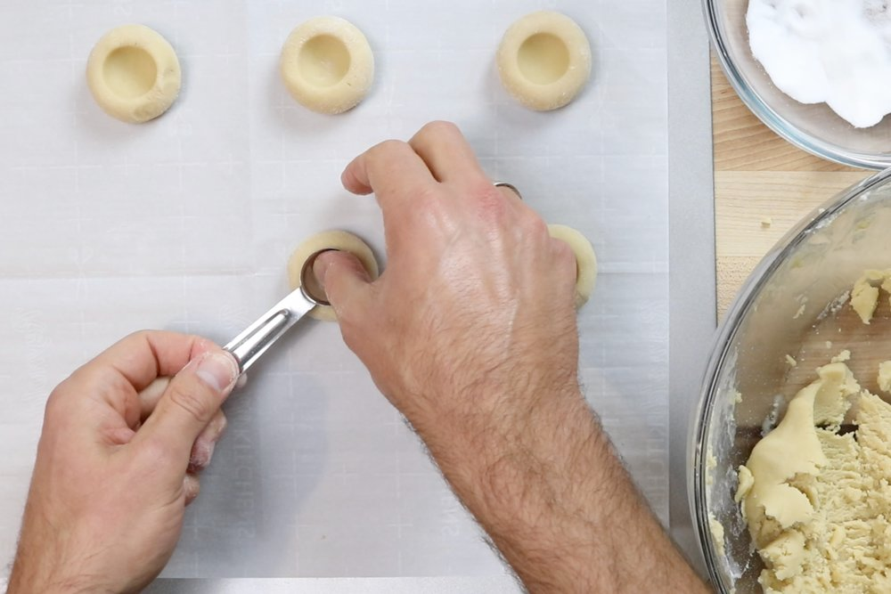 9. Use your thumb or the rounded back of a teaspoon to gently press an indent in the center of the cookie. -