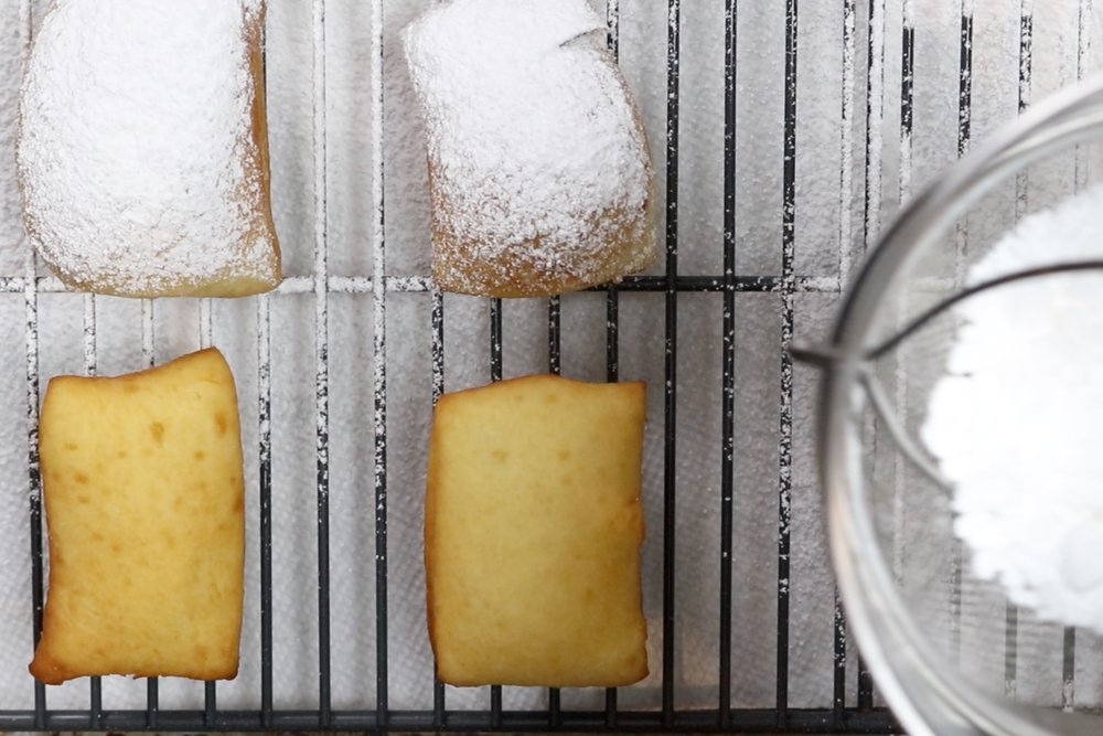 11. Drain the biegnets on a wire rack and let cool briefly before dusting them generously with powdered sugar. -