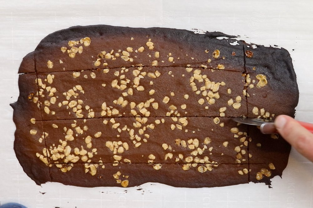 12. Remove from oven. Using a sharp knife or a pizza cutter, trim off the burned edges and cut the brittle into pieces. -