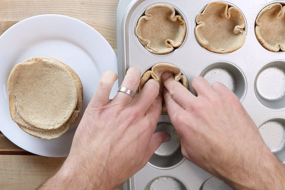 6. Press the bun halves cut side up in the tin. -