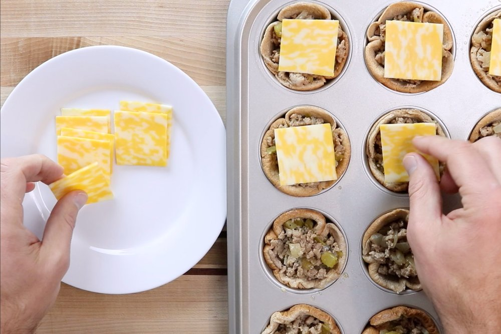 8. Quarter the 3 cheese slices into 12 equal squares and place one on each burger. -