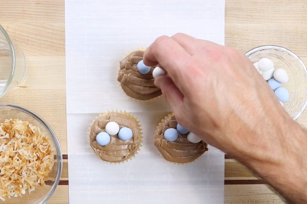4.  Gently press Cadbury Mini Eggs into the center of each cupcake with the pointed end facing down. -