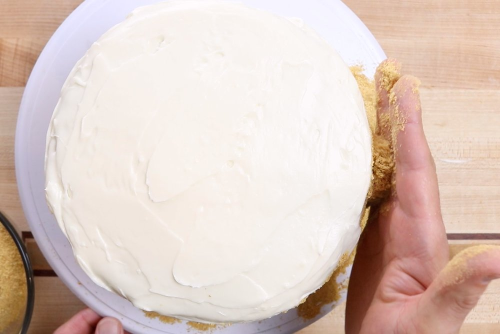4. Use the palm of your hand to cup crushed graham crackers around the edge of the cake.  (optional) -