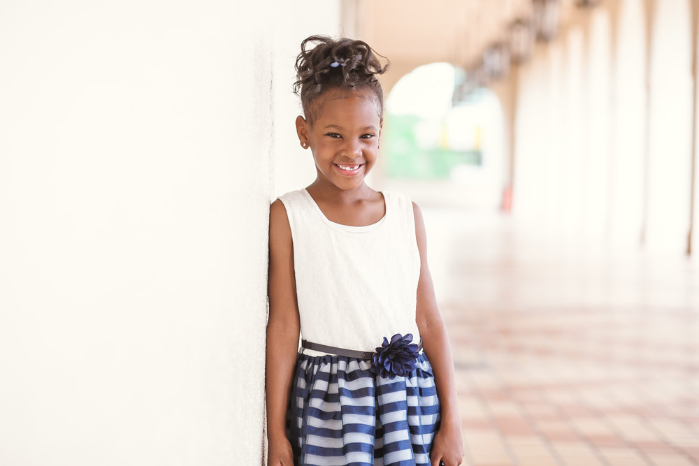 Happy girl leaning on wall at History Miami Museum gets adopted