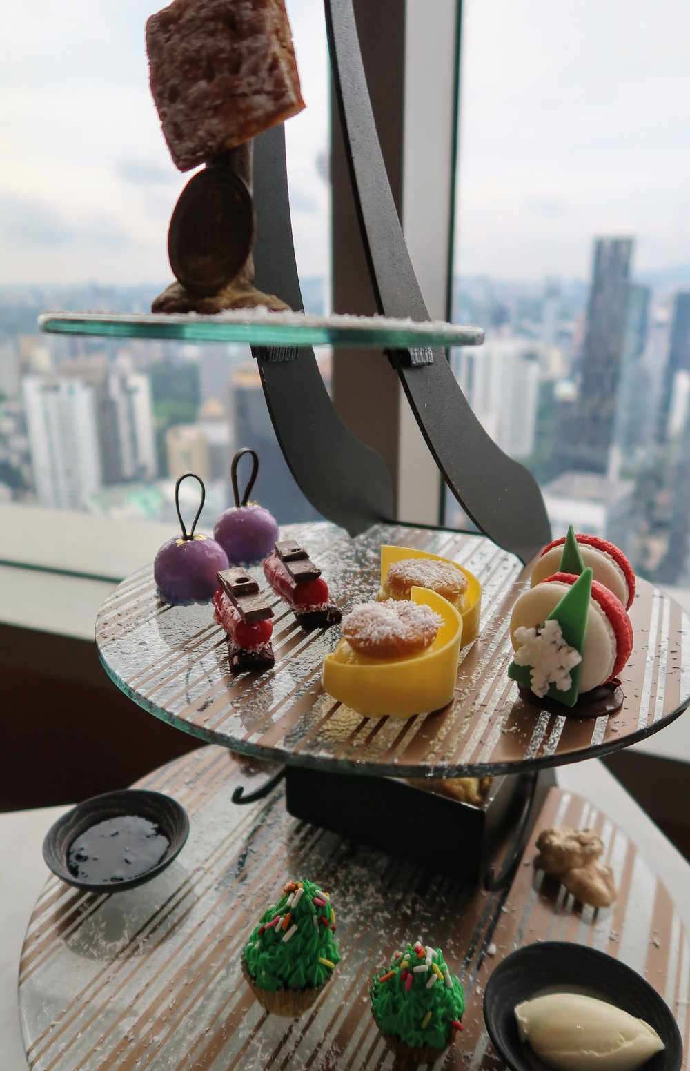 The sweets are served in a modern and fancy stand, like a grand masterpiece of artwork.