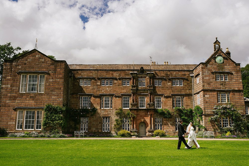 browsholme hall with bride and groom walking across grass