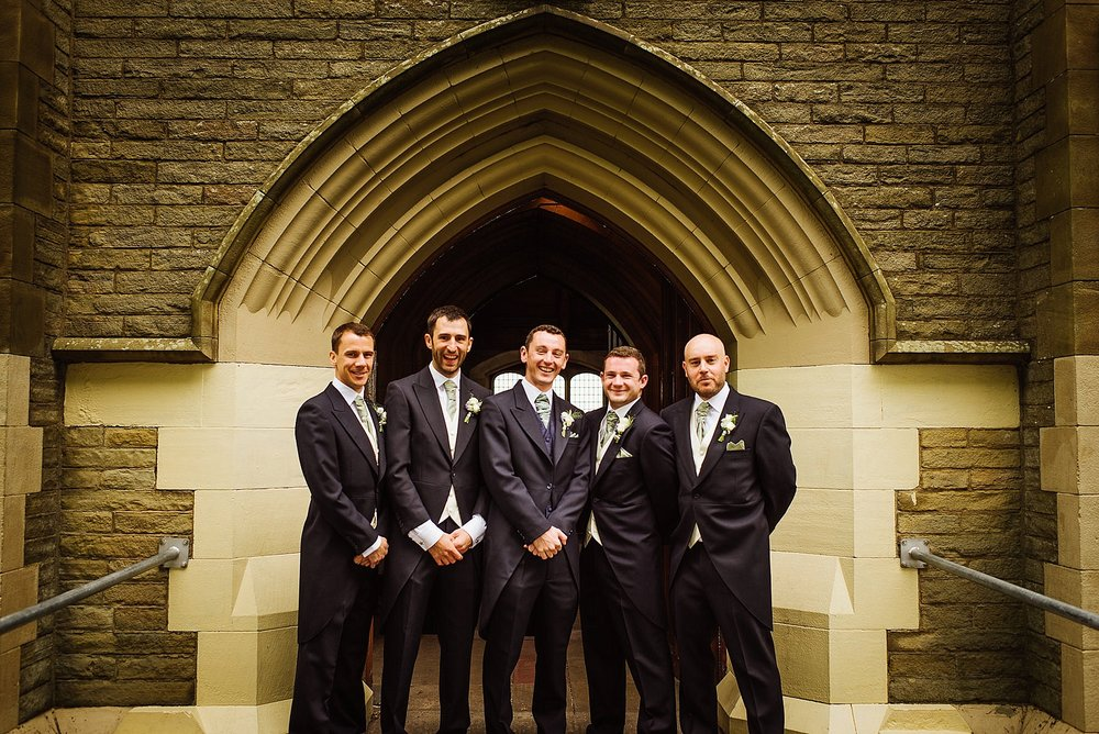 Five grooms men stood outside a church doorframe