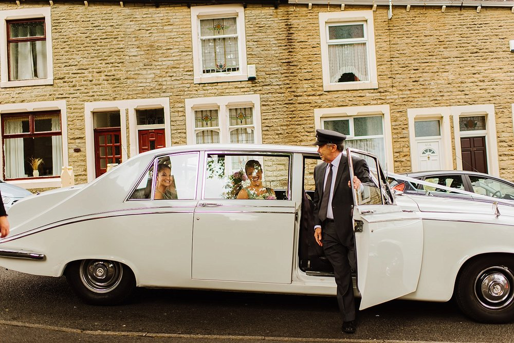 bridesmaids in a wedding car on a street with a row of terraced houses behind