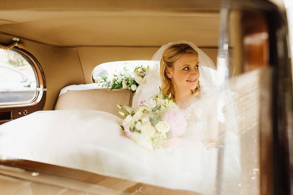 bride sat in car with wedding flowers