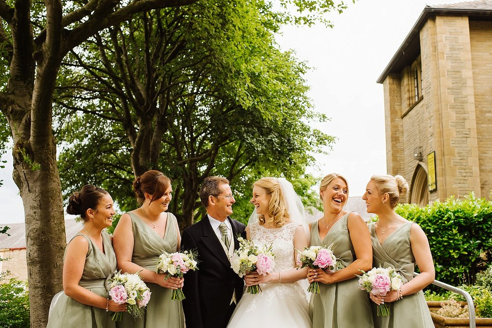 a bride with her father and four bridesmaids laughing outside a St Mary Magdalens C-of-E Church