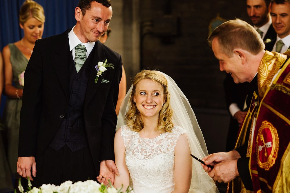 bride and groom smiling at the vicar